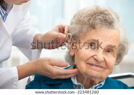 Doctor inserting hearing aid in senior's ear - stock photo