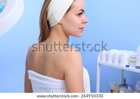 Doctor inspecting woman patient skin on her for melanoma - stock photo