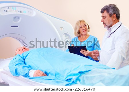 doctor instructing medical staff about CT scanner procedure - stock photo