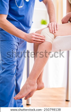 Doctor is rewinding knee bandage to young woman. - stock photo