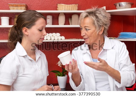 doctor is teaching an assistant something in a office, with medicine equipment