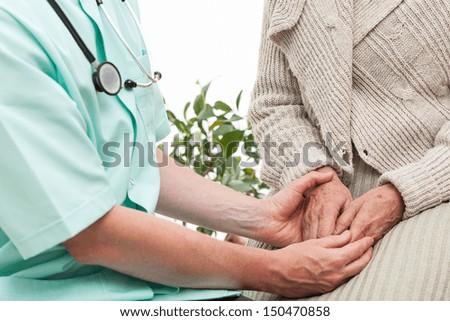 Doctor keeping an elderly patient's hands - stock photo
