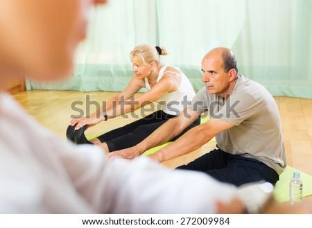 Doctor keeping eye at senior couple during training at gym. Focus on man  - stock photo