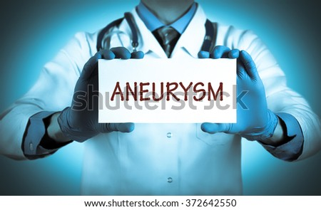 Doctor keeps a card with the name of the diagnosis -?? aneurysm. Selective focus. Medical concept. - stock photo