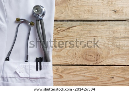 Doctor lab white coat pocket with pen, stethoscope, close-up shot on vintage wooden background. Copy space - stock photo