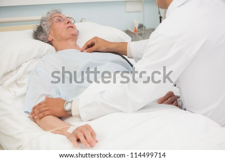 Doctor listening to heartbeat of elderly female patient in hospital bed - stock photo