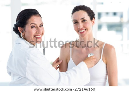 Doctor listening to patients chest with stethoscope in medical office - stock photo