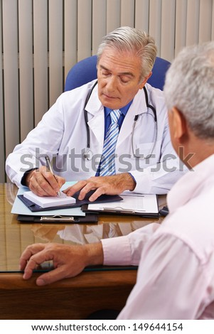 Doctor listening to senior patient and taking notes in his office - stock photo