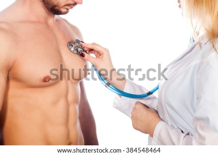 Doctor listening to young patient chest with stethoscope in his office at the hospital. - stock photo