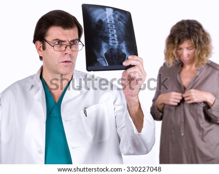 Doctor looking at a radiograph with the patient in the background - stock photo