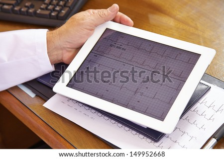 Doctor looking at ECG on a tablet computer in his office - stock photo