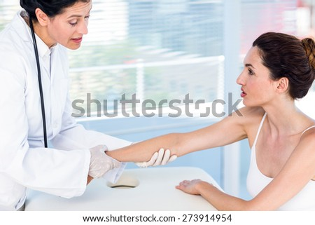 Doctor looking at her patients arm in medical office