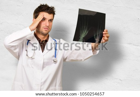 Doctor Looking At X-ray Against Wall