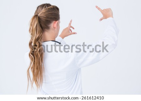 Doctor looking through finger frame on white background