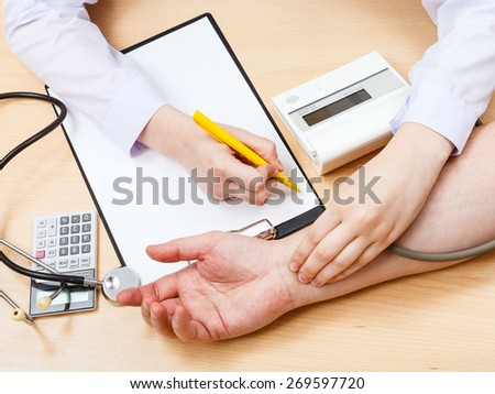 doctor makes appointment and measures blood pulse of patient - stock photo