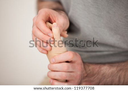 Doctor manipulating the fingers of a patient in his office