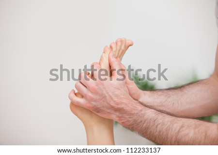 Doctor manipulating the foot of his patient in a room