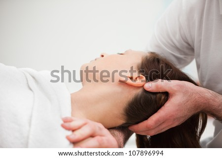 Doctor manipulating the neck of a woman in a room - stock photo