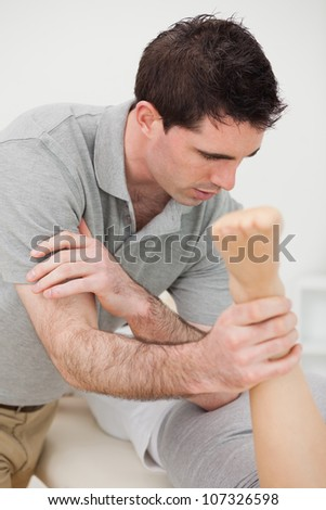 Doctor massaging a patient with his elbow in a room - stock photo