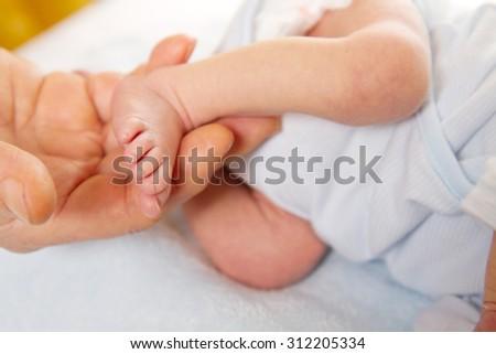 Doctor massaging little baby's foot - stock photo