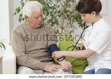 Doctor measuring blood pressure of elder man - stock photo