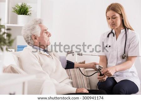 Doctor measuring blood pressure of elder man - stock photo
