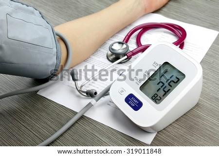 Doctor measuring blood pressure of patient, Digital Blood Pressure Monitor on wood background, Medical equipment, Examining equipment. - stock photo