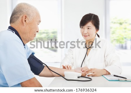 doctor measuring blood pressure of senior man at home - stock photo