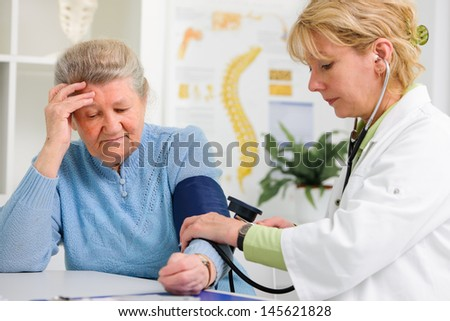 Doctor measuring blood pressure of senior patient - stock photo