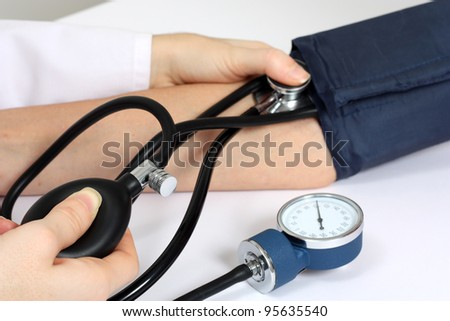 Doctor measuring patient blood pressure - stock photo