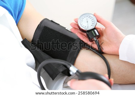 Doctor measuring patient pressure close up - stock photo