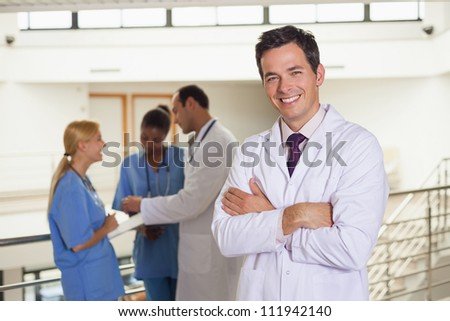 Doctor next to medical team in hospital corridor - stock photo