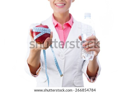 Doctor nutritionist holding apple with a tape measure on it and  bottle of water. Selective focus, isolated on white background. - stock photo