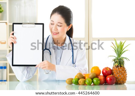 Doctor nutritionist with fruits and holding blank clipboard, healthy eating