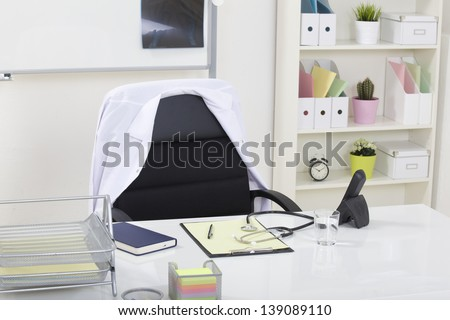 Doctor office table desk and black chair with stethoscope  and white paper - stock photo