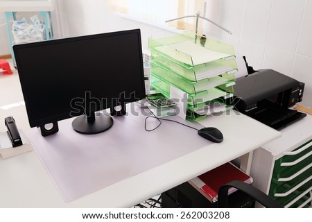 Doctor office table with office tools, monitor, mouse - stock photo