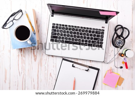 Doctor office,Top view ,Laptop (notebook) with cup of coffee and notepad,book with pen and  stethoscope with medicine on wood table. - stock photo