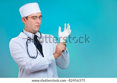 doctor on white background putting on blue latex gloves - stock photo