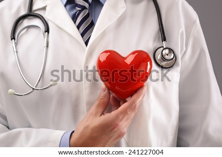 Doctor or cardiologist holding heart against chest concept for healthcare and diagnosis medical cardiac pulse test - stock photo