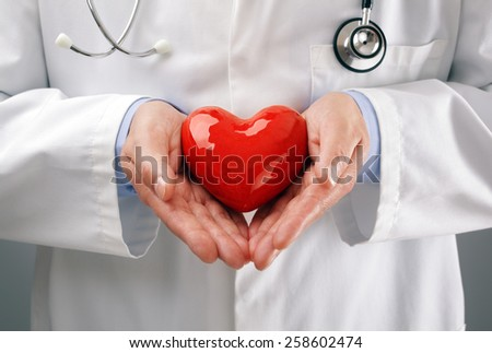 Doctor or cardiologist holding heart with care in hands concept for healthcare and diagnosis medical cardiac pulse test - stock photo