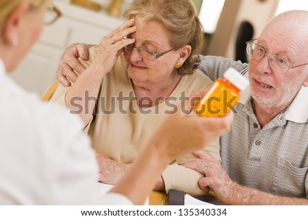 Doctor or Nurse Explaining Prescription Medicine to Attentive Senior Couple. - stock photo