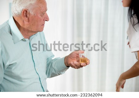 Doctor passes urine cups to patients - stock photo