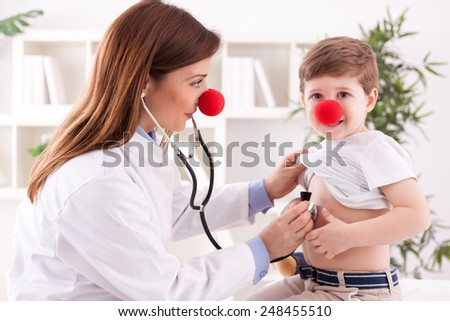 Doctor pediatrician and patient happy child with clown noses