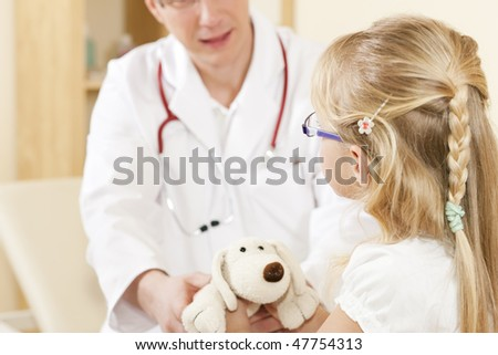 Doctor - Pediatrician - with a child patient in his practice, she is ging him her soft toy as to thank him