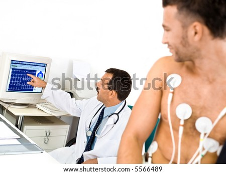 Doctor performing an EKG test on young male patient. Real people, real location, not a staged photo with models. - stock photo