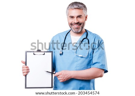 Doctor pointing clipboard. Cheerful mature doctor looking at camera and smiling while pointing copy space on his clipboard and standing isolated on white - stock photo