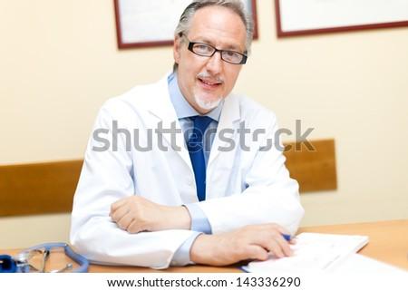 Doctor portrait in his studio - stock photo