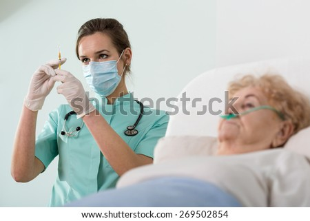 Doctor preparing to do an  injection on an elderly patient - stock photo