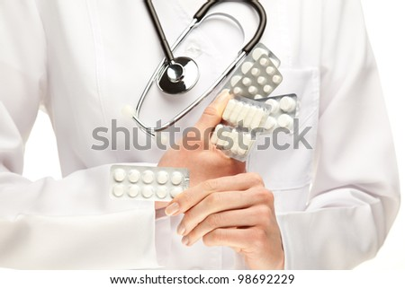 Doctor prescribing many pills; doctor's hands holding many medicines