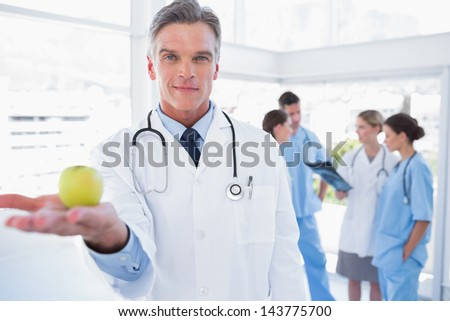 Doctor presenting an apple in his hand in front of his medical team - stock photo